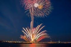 Os fogos-de-artifício brilhantes estouraram no céu azul que cria círculos múltiplos da luz e fugas de luz fotografia de stock royalty free