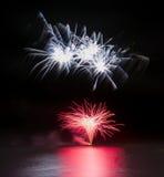 Os fogos-de-artifício indicam sobre o mar com reflexões na água Fotografia de Stock Royalty Free