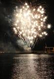 Os fogos-de-artifício refletem na água do mar imagem de stock