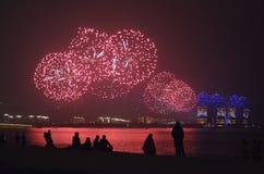 Os fogos de artif?cio vermelhos refletiram nas ?guas do mar do Sul da China imagens de stock