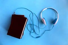 Os fones de ouvido azuis são conectados ao livro para escutar imagem de stock