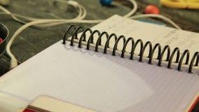 Os fones de ouvido brancos, o caderno para notas e os doces esverdeiam, vermelho, amarelo video estoque