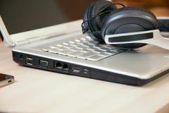 Os fones de ouvido estão no portátil Imagens de Stock Royalty Free