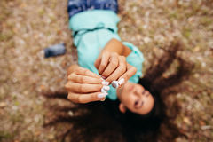 Os fones de ouvido fecham-se acima na opinião superior aérea das mãos da menina Fotografia de Stock Royalty Free