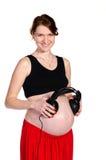 Os fones de ouvido guardando grávidos aproximam a barriga Imagens de Stock