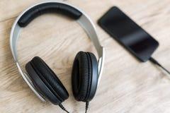 Os fones de ouvido modernos conectaram ao jogador de música na tabela de madeira Foto de Stock Royalty Free