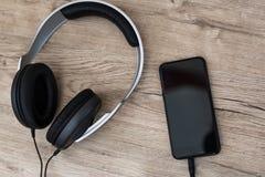 Os fones de ouvido modernos conectaram ao jogador de música na tabela de madeira Imagens de Stock