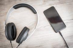 Os fones de ouvido modernos conectaram ao jogador de música na tabela de madeira Fotos de Stock Royalty Free