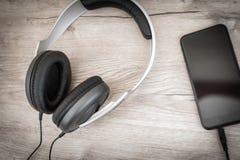 Os fones de ouvido modernos conectaram ao jogador de música na tabela de madeira Fotografia de Stock Royalty Free