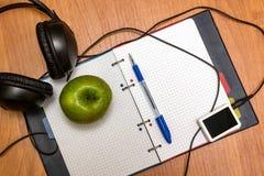 Os fones de ouvido, o jogador de música, a pena e a maçã encontram-se no caderno escola Imagens de Stock Royalty Free