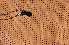 Os fones de ouvido pretos encontram-se no sportswear alaranjado da fibra do nylon do poliéster O conceito da escuta a música dura imagem de stock royalty free