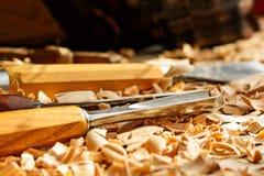 Os formões colocaram em aparas de madeira na mesa imagem de stock royalty free