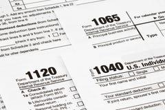 Os formulários de imposto com dinheiro e a pena Conceito do dia do imposto foto de stock