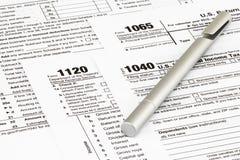 Os formulários de imposto com dinheiro e a pena Conceito do dia do imposto imagem de stock
