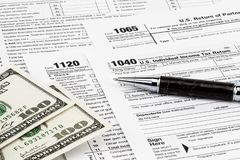 Os formulários de imposto com dinheiro e a pena Conceito do dia do imposto imagens de stock royalty free