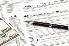 Os formulários de imposto com dinheiro e a pena Conceito do dia do imposto fotografia de stock