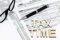 Os formulários de imposto com os vidros, dinheiro e a pena Conceito do dia do imposto foto de stock
