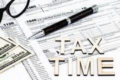 Os formulários de imposto com os vidros, dinheiro e a pena Conceito do dia do imposto imagem de stock royalty free