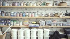 Os frascos com cores estão em prateleiras na oficina da arte dentro filme