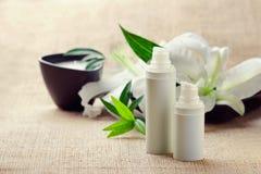 Os frascos de desnatam/loções/soros e lilys fotografia de stock