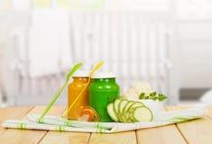 Os frascos de vegetais do puré do bebê no fundo iluminam a madeira Foto de Stock