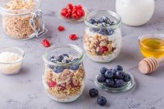 Os frascos de vidro da aveia lascam-se com fruto fresco, iogurte e mel Fotografia de Stock