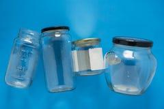 Os frascos de vidro isolados colocaram horizontalmente e centro no fundo azul - reciclar o programa imagem de stock