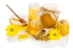Os frascos do mel com favos de mel, bacia de vidro com mel Foto de Stock Royalty Free