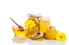 Os frascos do mel com favos de mel, bacia de vidro com mel Fotografia de Stock Royalty Free