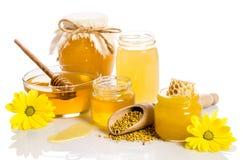 Os frascos do mel com favos de mel, bacia de vidro com mel Imagem de Stock