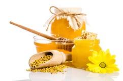 Os frascos do mel com favos de mel, bacia de vidro com mel Fotos de Stock