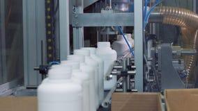 Os frascos plásticos brancos estão movendo-se ao longo da correia transportadora filme