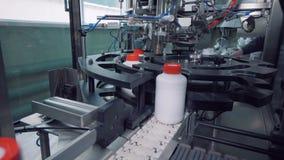 Os frascos plásticos brancos estão obtendo fechados mecanicamente com tampões vídeos de arquivo