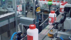 Os frascos plásticos estão obtendo envolvidos acima com fita video estoque