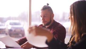 Os freelancers masculinos e fêmeas discutem originais do trabalho e da revisão, freelancers felizes video estoque