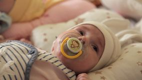 Os gêmeos bonitos dos bebês estão na fase e sugam em uma chupeta filme