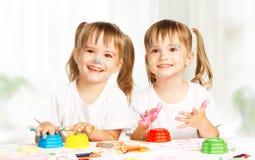 Os gêmeos felizes das crianças tiram pinturas, obtêm sujos fotos de stock royalty free