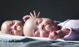 Os gêmeos recém-nascidos bonitos menino e menina estão encontrando-se na cama contra um fundo escuro Com tonificação e borrão imagens de stock royalty free