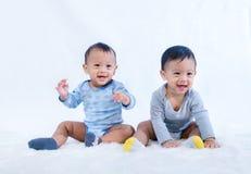Os gêmeos recém-nascidos sentam-se para baixo Os gêmeos recém-nascidos dos bebês sentam-se para baixo na cama Bonito sente-se par fotos de stock