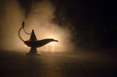 Os gênios antigos das noites árabes de Aladdin denominam a lâmpada de óleo com fumo branco da luz suave, fundo escuro Lâmpada do  Fotografia de Stock Royalty Free