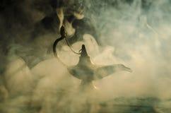 Os gênios antigos das noites árabes de Aladdin denominam a lâmpada de óleo com fumo branco da luz suave, fundo escuro Lâmpada do  Imagem de Stock