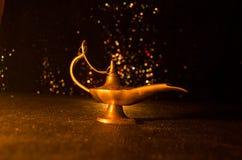 Os gênios antigos das noites árabes de Aladdin denominam a lâmpada de óleo com fumo branco da luz suave, fundo escuro Lâmpada do  Foto de Stock