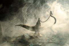 Os gênios antigos das noites árabes de Aladdin denominam a lâmpada de óleo com fumo branco da luz suave, fundo escuro Lâmpada do  Imagens de Stock