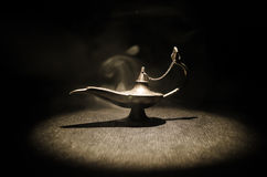 Os gênios antigos das noites árabes de Aladdin denominam a lâmpada de óleo com fumo branco da luz suave, fundo escuro Lâmpada do  Fotografia de Stock