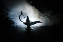 Os gênios antigos das noites árabes de Aladdin denominam a lâmpada de óleo com fumo branco da luz suave, fundo escuro Lâmpada do  Fotos de Stock Royalty Free