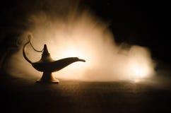 Os gênios antigos das noites árabes de Aladdin denominam a lâmpada de óleo com fumo branco da luz suave, fundo escuro Lâmpada do  Fotos de Stock