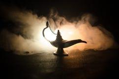Os gênios antigos das noites árabes de Aladdin denominam a lâmpada de óleo com fumo branco da luz suave, fundo escuro Lâmpada do  Imagem de Stock Royalty Free