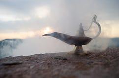Os gênios artisanal antigos das noites de Aladdin Arabian denominam a lâmpada de óleo com fumo do branco da luz suave Fundo da mo Foto de Stock Royalty Free