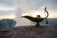 Os gênios artisanal antigos das noites de Aladdin Arabian denominam a lâmpada de óleo com fumo do branco da luz suave Fundo da mo Foto de Stock