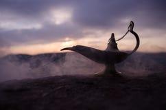 Os gênios artisanal antigos das noites de Aladdin Arabian denominam a lâmpada de óleo com fumo do branco da luz suave Fundo da mo Fotos de Stock